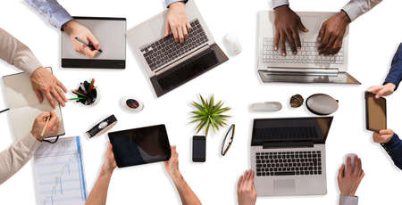 High Angle View Of Businesspeople Hand Working On Electronic Devices