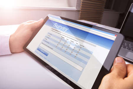 Close-up Of Persons Hand Holding Digital Tablet Showing Survey Form On Desk Banque d'images