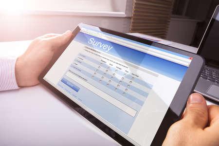 Close-up Of Persons Hand Holding Digital Tablet Showing Survey Form On Desk Standard-Bild