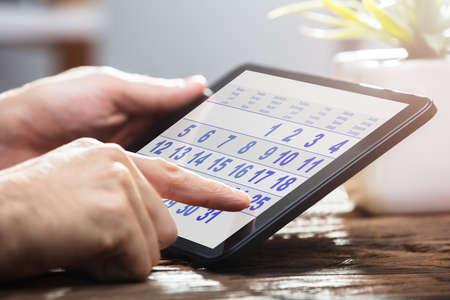 Gros plan de la main d'un homme d'affaires à l'aide de calendrier sur tablette numérique