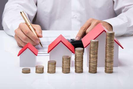 Close-up, de, homem negócios, calculando, fatura, com, diferente tamanho, casas, e, pilhas, de, moedas, ligado, tabela