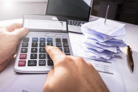 Close-up Of A Persons Hand Calculating Invoice Near Bills And Laptop In Office