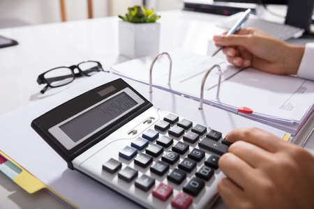 Close-up Of Businessperson Calculating Bills With Calculator In Office Banque d'images