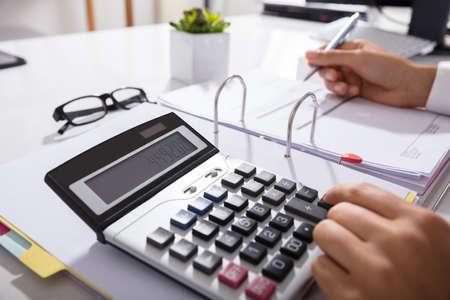 Close-up Of Businessperson Calculating Bills With Calculator In Office Standard-Bild