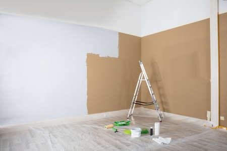 Half Painted White Wall With Ladder And Painting Equipments At Home Banco de Imagens - 93316269