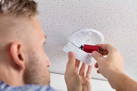 Close-up Of A Persons Hand Inserting Battery In Smoke Detector