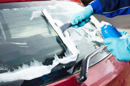 Close-up Of Persons Hand Washing Rear Windshield Of A Car Using Squeegee Banque d'images