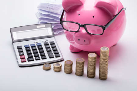 Close-up Of Stacked Coins With Piggy Bank And Calculator On Desk Standard-Bild