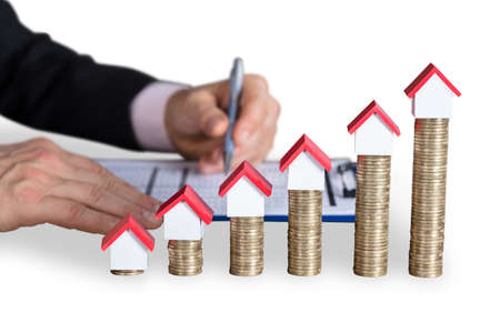 House Model On Top Of Stacked Coins Near Persons Hand Writing On Document