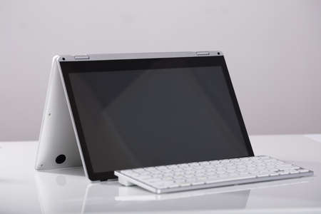 Close-up Of Blank Hybrid Laptop With External Over The White Desk At Workplace