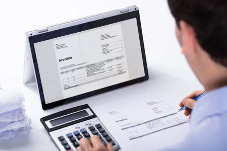 Close-up Of Businessman Calculating The Invoice Using Hybrid Laptop And Calculator At Workplace