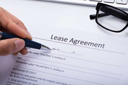 Close-up Of A Persons Hand Filling Lease Agreement Form Stock Photo