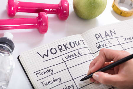 Woman Writing Workout Plan In Notebook At Wooden Desk