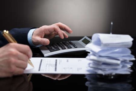 Businessperson Checking Invoice With Receipts On Desk