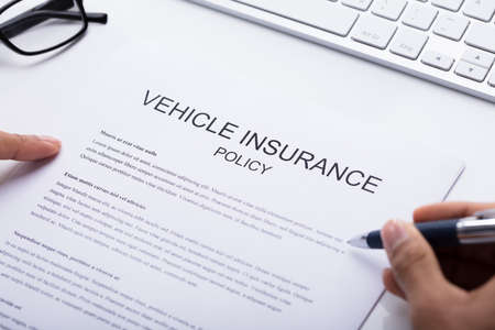 Close-up Of A Persons Hand Filling Vehicle Insurance Policy Form