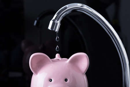 Water Dripping From The Faucet Inside The Piggybank Over The Black Background