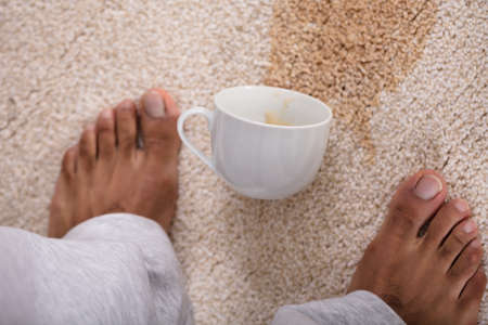 Close-up Of A Persons Feet Standing Near Spilled Coffee On Carpet Banque d'images