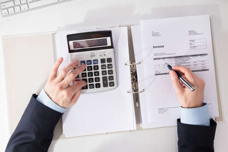 Close-up Of A Businesspersons Hand Checking Invoice With Calculator At Workplace