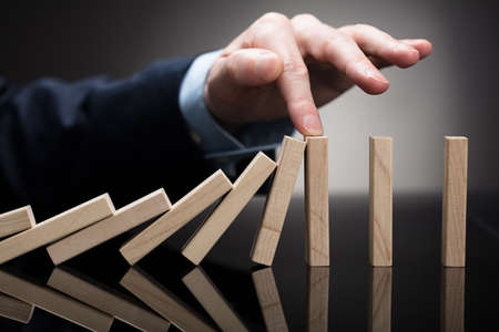 Close-up Of A Businessperson Stopping Wooden Blocks With His Finger From Falling On Desk Banque d'images