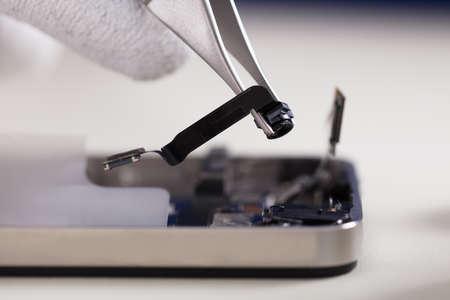 Close-up Of A Tweezers Changing Broken Camera Of Mobil Phone