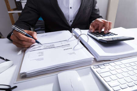 Close-up Of A Businesspersons Hand Calculating Bill With Calculator