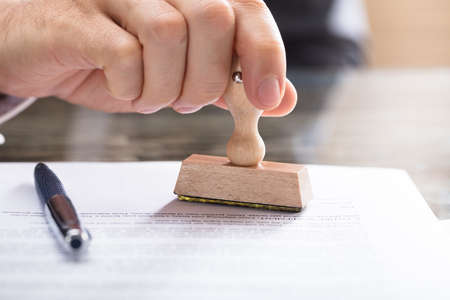 Close-up Of A Human Hand Stamping Document On Desk Standard-Bild