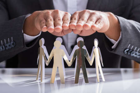 Close-up Of A Businesspersons Hand Protecting Cut-out Figures On Desk
