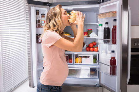 Pregnant Woman Eating Sandwich In Front Of Open Refrigerator Standard-Bild