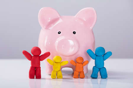 Row Of Colorful Clay Family In Front Of Pink Plastic Piggybank Over The White Desk