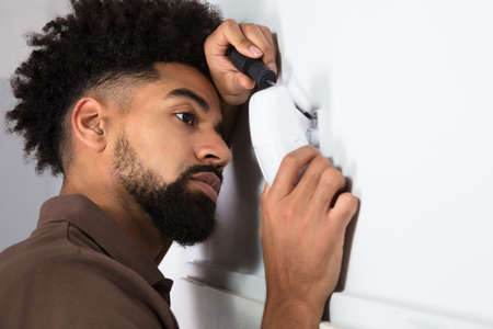 Side View Of A Male Technician Installing Security System Motion Sensor With Screwdriver