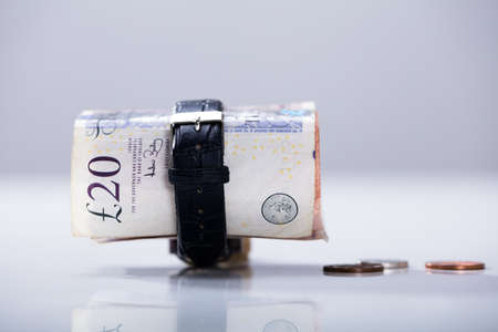 Close-up Of Rolled Up Twenty Pounds Currency Note Inside The Wrist Watch On The Desk