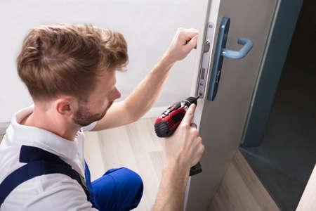 Young Carpenter Install Door Lock With Wireless Screwdriver Standard-Bild