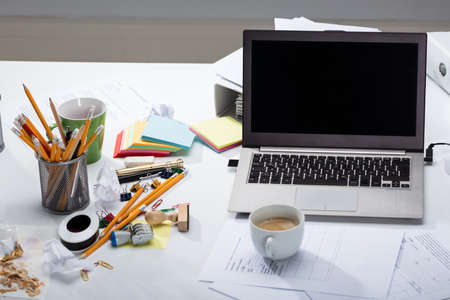Laptop And Coffee Cup On The Document Paper Over The Messy Desk In The Office