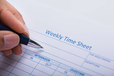 Close-up Of A Persons Hand Filling Blank Weekly Time Sheet With Pen Stock Photo