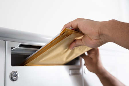 Close-up Of A Postmans Hand Putting Letters In Mailbox Stok Fotoğraf
