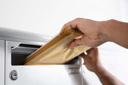 Gros plan de la main d'un postier mettant des lettres dans la boîte aux lettres Banque d'images - 93315637