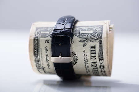 Rolled Up Dollar Banknote Tied With Belt Against White Background Archivio Fotografico