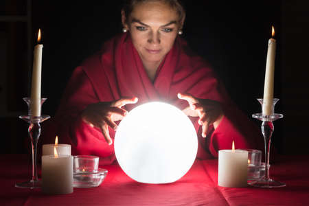 Beautiful Young Fortuneteller Holding Hands Around A Glowing Ball Foto de archivo