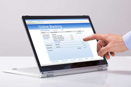 Close-up Of Males Hand Using Online Banking On Hybrid Laptop Over The White Desk