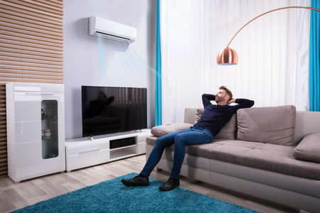 Young Man Relaxing On Sofa Near Television At Home Stockfoto