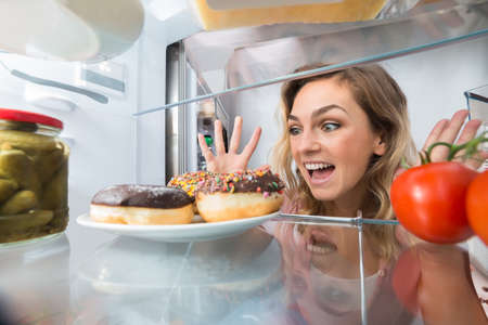 Excited Young Woman Looking At Donuts In Refrigerator