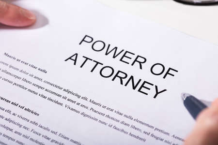 Close-up Of A Person Holding Pen Over Power Of Attorney Form Stok Fotoğraf - 93315419