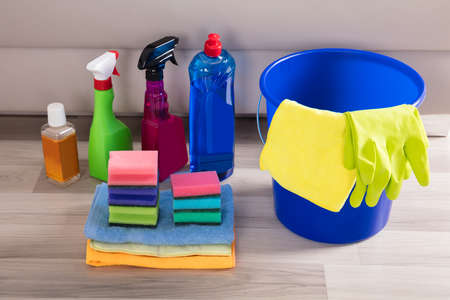 Blue Colored Bucket With Cleaning Equipments On Hardwood Floor
