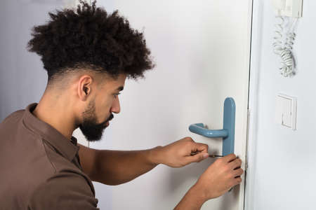 Close-up Of A Persons Hand Opening Door Lock With Lockpicker Stock Photo