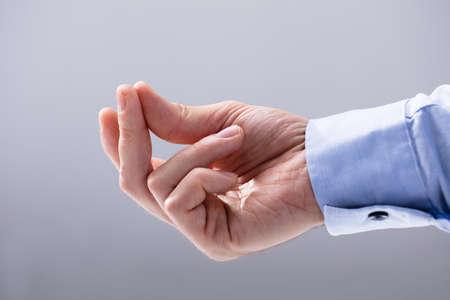 白い背景に指をスナップする男の手のクローズアップ 写真素材