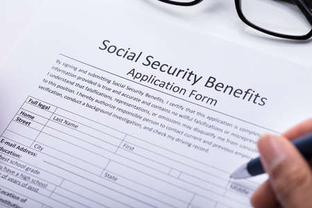 Close-up Of A Persons Hand Filling Social Security Benefits Application Form Stock Photo