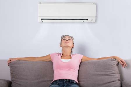 Telecomando felice della tenuta della giovane donna che si rilassa sotto il condizionatore d'aria
