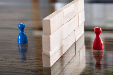 Close-up Of Red And Blue Figurine Paw Separated By Wooden Blocks On Desk