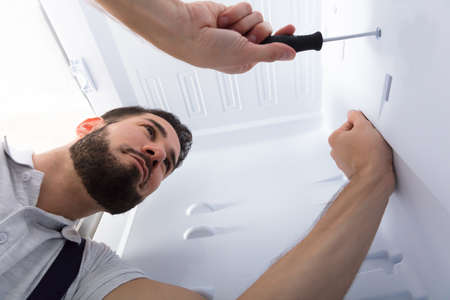 Close-up Of A Male Electrician Fixing Refrigerator In Kitchen Reklamní fotografie