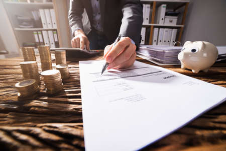 Close-up Of A Businesspersons Hand Signing Document With Stacked Golden Coins On Wooden Desk